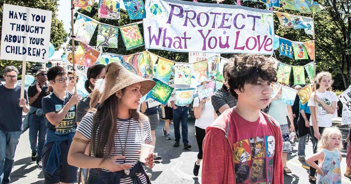 """People march against fossil fuel expansion under a banner that says """"Protect What You Love"""""""