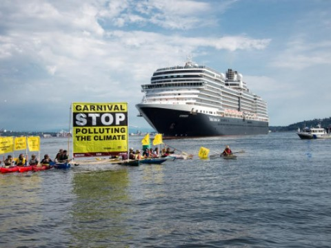 Protestors hold a banner calling out Carnival Corporation for polluting
