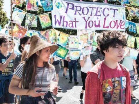 "People march against fossil fuel expansion under a banner that says ""Protect What You Love"""