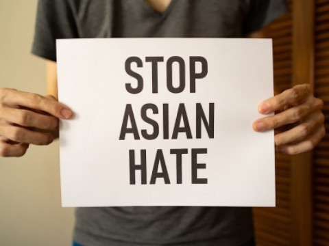 Person holds sign saying stop asian hate